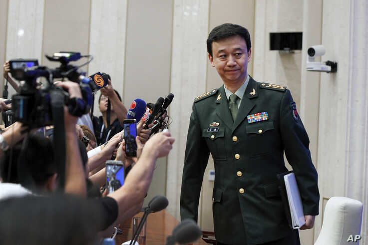 China's Defense Ministry spokesman Wu Qian leaves as journalists are asking question on Hong Kong's recent protests after a press conference at the State Council Information Office in Beijing, July 24, 2019.