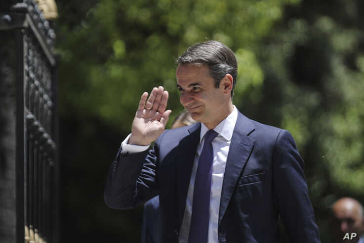 Greece's newly-elected prime minister Kyriakos Mitsotakis, waves as he walks shortly after his swearing-in ceremony at the Presidential Palace in Athens, Monday, July 8, 2019. Mitsotakis' New Democracy party won 39.8% of the vote, giving him 158…