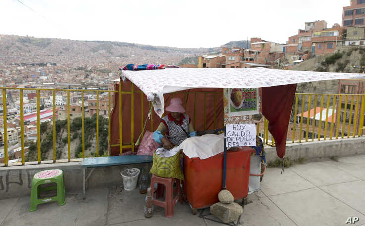 """A street vendor waits for customers at her stall, where she has a sign that reads in Spanish """"There is chicken and beef broth soup,"""" for about a little over $1, in La Paz, Bolivia, Wednesday, April 10, 2019. In an attempt to tackle a growing trade…"""