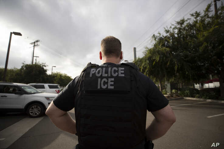 FILE - In this July 8, 2019, file photo, a U.S. Immigration and Customs Enforcement (ICE) officer looks on during an operation in Escondido, Calif. Advocacy groups and unions are pressuring Marriott, MGM and others not to house migrants who have…