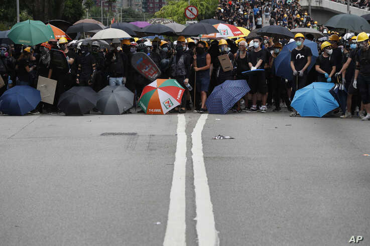 Protesters face off against riot police at the entrance to a village at Yuen Long district in Hong Kong, July 27, 2019. Protesters wearing black streamed through Yuen Long, even though police refused to grant permission for the march.