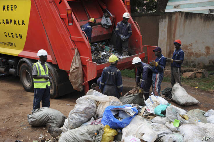 In this photo of Wednesday, July 10, 2019, workers of Kampala Capital City Authority remove garbage under a campaign encouraging people to keep their neighbourhood clean, in Makindye Lukuli area of Kampala, Uganda.  Africa faces a population boom…