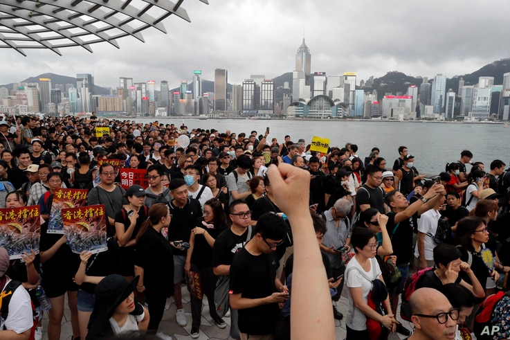 FILE - Protesters march near the skyline of Hong Kong, July 7, 2019. China's central government has dismissed Hong Kong pro-democracy protesters as clowns and criminals while bemoaning growing violence surrounding the monthslong demonstrations.