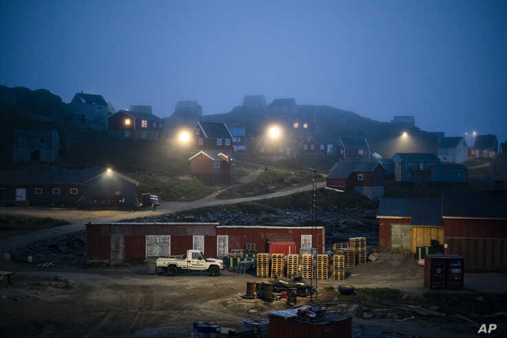 FILE - In this Aug. 15, 2019, file photo, early morning fog shrouds homes in Kulusuk, Greenland. As warmer temperatures cause the ice to retreat the Arctic region is taking on new geopolitical and economic importance, and not just the United States…
