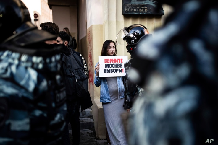 """FILE - In this file photo taken on Saturday, Aug. 10, 2019, A woman holds a poster reading """"Give us back our elections in Moscow!"""" in front of police during a protest in Moscow, Russia. Ella Pamfilova, head of Russian Central Election Commission,…"""