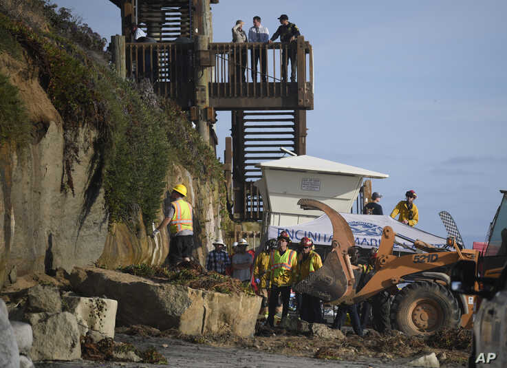 Search and rescue personnel work at the site of a cliff collapse at a popular beach, Aug. 2, 2019, in Encinitas, Calif.