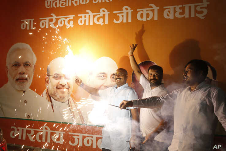 Supporters of India's ruling Bharatiya Janata Party (BJP) light firecrackers and celebrate the government revoking Kashmir's special status, in Lucknow, India, Tuesday, Aug. 6, 2019. Indian lawmakers passed a bill Tuesday that strips the statehood…