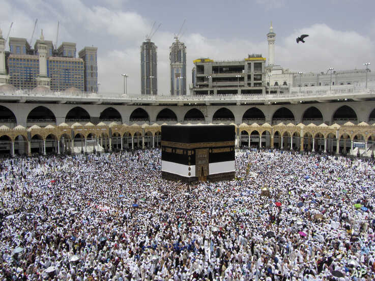 FILE - In this Thursday, Aug. 8, 2019 file photo, Muslim pilgrims circumambulate around the Kaaba, the cubic building at the Grand Mosque, ahead of the Hajj pilgrimage in the Muslim holy city of Mecca, Saudi Arabia. Over 2 million Muslims from…