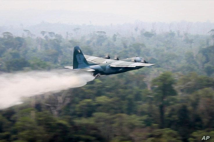In this photo released by Brazil Ministry of Defense, a C-130 Hercules aircraft dumps water to fight fires burning in the Amazon rainforest, in Brazil, Saturday, Aug, 24, 2019. Backed by military aircraft, Brazilian troops on Saturday were deploying…
