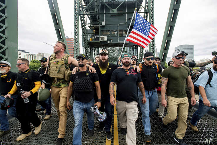 """Members of the Proud Boys and other right-wing demonstrators march across the Hawthorne Bridge during an """"End Domestic Terrorism"""" rally in Portland, Ore., on Saturday, Aug. 17, 2019. The group includes organizer Joe Biggs, in green hat, and Proud…"""