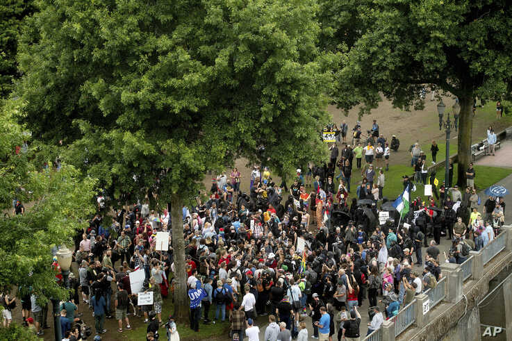 """Right-wing demonstrators and counter-protesters gather in Tom McCall Waterfront Park during an """"End Domestic Terrorism"""" rally in Portland, Ore., on Saturday, Aug. 17, 2019.  Police seized metal poles, bear spray and other weapons as hundreds of far…"""