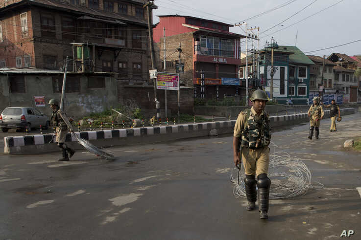 Indian Paramilitary soldiers drag barbwire as they prepare to impose curfew in Srinagar, Indian controlled Kashmir, Wednesday, Aug. 7, 2019. Authorities in Hindu-majority India clamped a complete shutdown on Kashmir as they scrapped the Muslim…