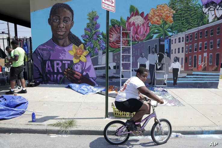 A boy rides his bicycle, July 29. 2019, after volunteering to paint a mural outside the New Song Community Church in the Sandtown section of Baltimore.