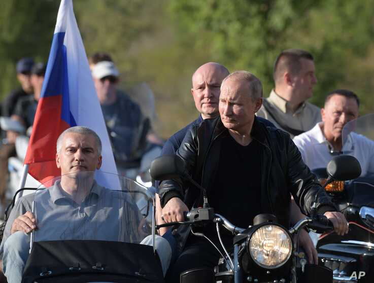 Russian President Vladimir Putin drives a motorbike during the Babylon's Shadow bike show camp near in Sevastopol, Crimea, Aug. 10, 2019.