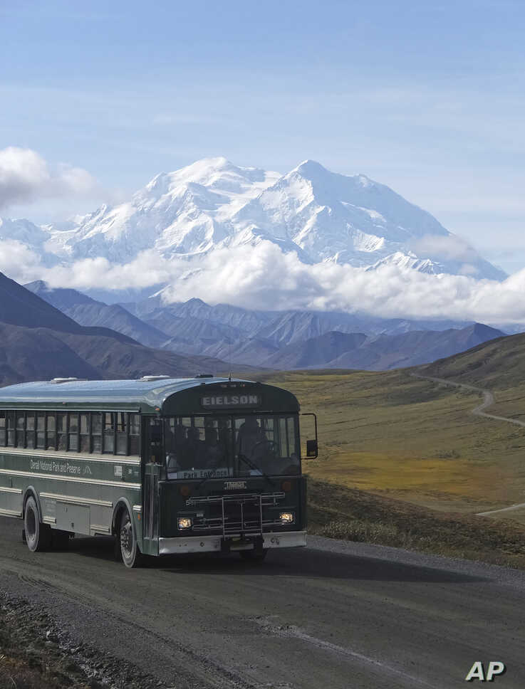 In this Aug. 26, 2016, photo, a shuttle bus carrying tourists makes its way along the park road with North America's tallest peak, Denali, in the background, in Denali National Park and Preserve, Alaska. President Barack Obama's administration in…
