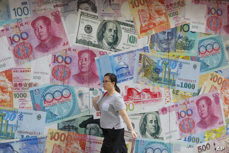 A woman walks by a money exchange shop decorated with different countries currency banknotes at Central, a business district in Hong Kong, Tuesday, Aug. 6, 2019. China's yuan fell further Tuesday against the U.S. dollar, fueling fears about…