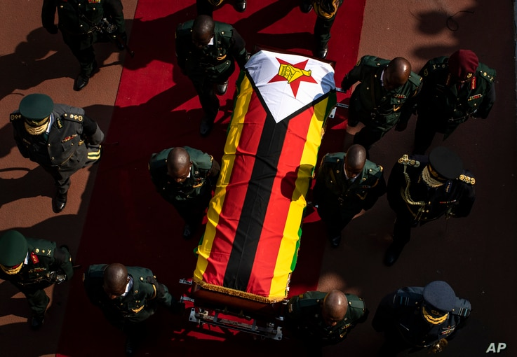 FILE - In this Sept. 14, 2019, file photo, the casket of former president Robert Mugabe is escorted by military officers as it departs after a state funeral at the National Sports Stadium in the capital Harare, Zimbabwe. After 16 years in…