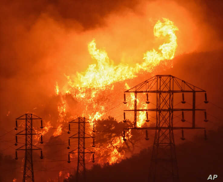 FILE - In this Dec. 16, 2017, file photo provided by the Santa Barbara County Fire Department, flames burn near power lines in Sycamore Canyon near West Mountain Drive in Montecito, Calif. As California counties face the prospect of increased…