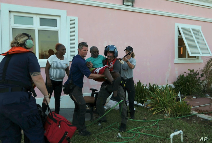 Members of US' Coast Guard evacuate a man from a hospital in Marsh Harbor, Abaco Island, Bahamas, Friday, Sept. 6, 2019. The Bahamian health ministry said helicopters and boats are on the way to help people in affected areas, though officials warned…