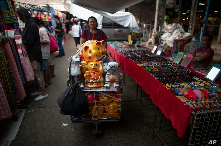 A mobile street vender pushes a cart with piggy banks in a market in Bangkok, Thailand, Sept. 4, 2019.