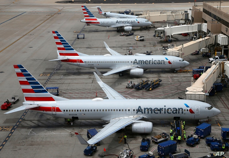 FILE - This July 17, 2019, file photo shows American Airlines planes at Phoenix Sky Harbor International Airport in Phoenix. American Airlines wants two labor unions to pay damages and the company's attorney fees, saying they ignored a judge's order…