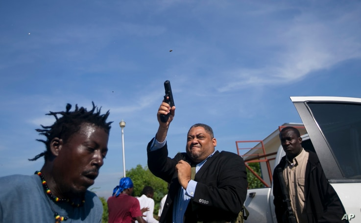 Ruling party Senator Ralph Fethiere fires his gun outside Parliament as he arrives for a vote on the ratification of Fritz William Michel's nomination as prime minister in Port-au-Prince, Haiti, Monday, Sept. 23, 2019. Opposition members confronted…