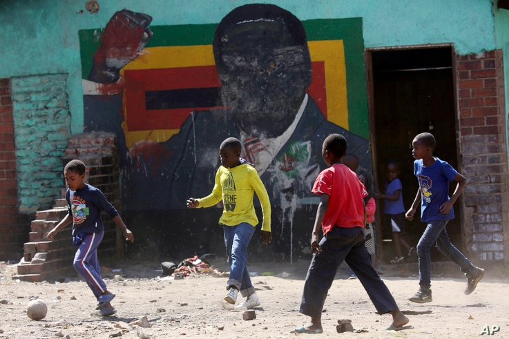 FILE - In this Friday, Sept. 6, 2019, file photo, children play soccer next to a defaced portrait of former Zimbabwean president Robert Mugabe in Harare, Zimbabwe. After 16 years in journalistic exile, Andrew Meldrum returned to Zimbabwe, the…
