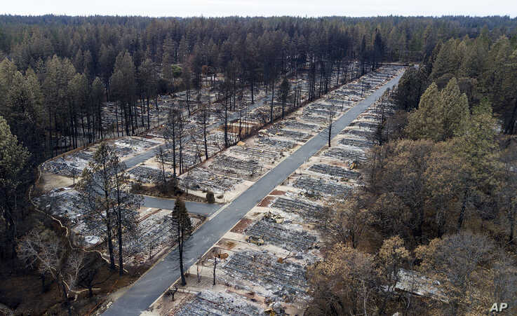FILE- in this Dec. 3, 2018, file photo, homes leveled by the Camp Fire line the Ridgewood Mobile Home Park retirement community in Paradise, Calif. As California counties face the prospect of increased utility power shut-off meant to prevent…