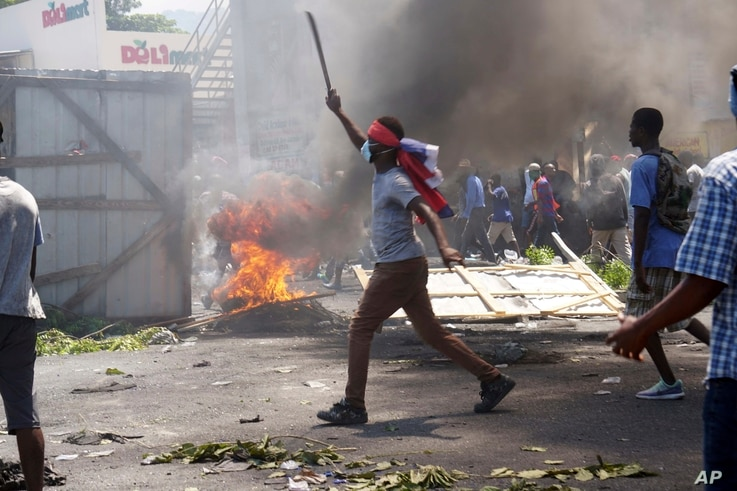 A masked protester wields a machete during a protest to demand the resignation of President Jovenel Moise in Port-au-Prince, Haiti, Friday, Sept. 27, 2019. Thousands of protesters attacked businesses and government buildings across Haiti Friday,…