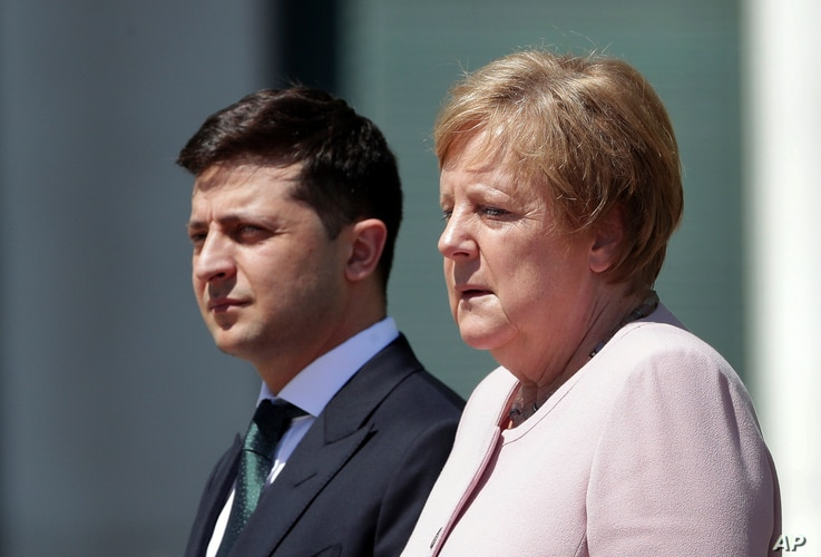 German Chancellor Angela Merkel, right, and Ukraine's President Volodymyr Zelenskiy, left, attend the national anthems as part of a military welcome ceremony in Berlin, Germany, Tuesday, June 18, 2019. Merkel appeared unwell as she met with…