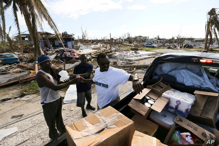 Volunteers handout food and water to the survivors of Hurricane Dorian in Marsh Harbor, Abaco Island, Bahamas, Friday, Sept. 6, 2019. The Bahamian health ministry said helicopters and boats are on the way to help people in affected areas, though…