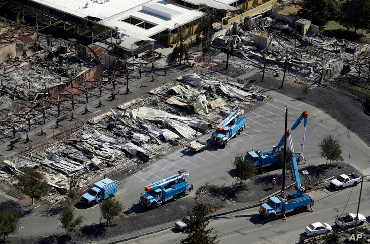 FILE - In this Oct. 14, 2017, file photo, Pacific Gas & Electric, PG&E crews work on restoring power lines in a fire ravaged neighborhood in an aerial view in the aftermath of a wildfire in Santa Rosa, Calif. , As California counties face the…