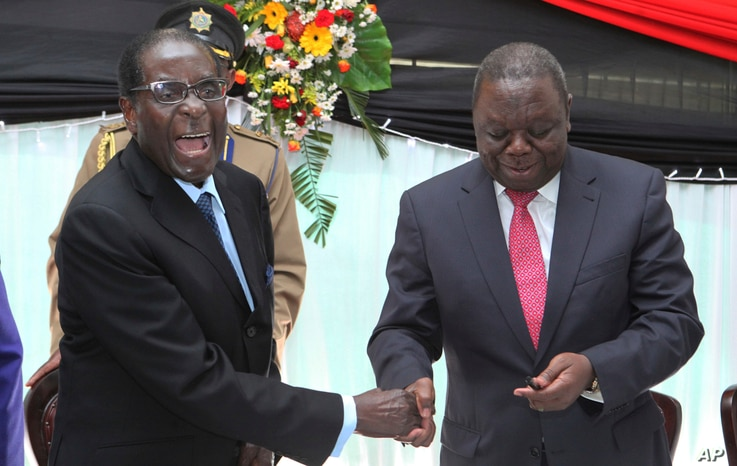 FILE - In this Wednesday, May 22, 2013 file photo Zimbabwean President Robert Mugabe, left, shakes hands with Prime Minister Morgan Tsvangirai after he signed the new constitution into law at State house in Harare. On Friday, Sept. 6, 2019, Zimbabwe…