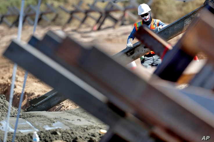 A government contractor, surrounded by existing Normandy barriers that separate Mexico and the United States, pours a concrete footer in preparation for a section of Pentagon-funded border wall along the Colorado River, Tuesday, Sept. 10, 2019 in…