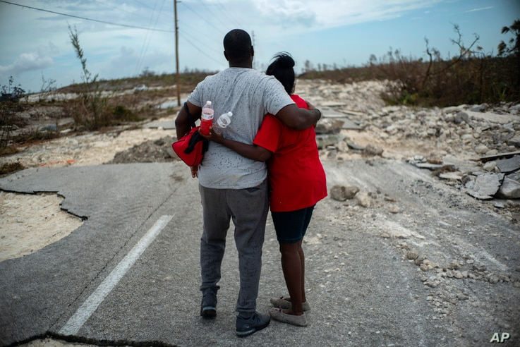 A couple embraces on a road destroyed by Hurricane Dorian, as they walk to the town of High Rock to try and find their relatives in the aftermath of Hurricane Dorian, in Grand Bahama, Bahamas, Thursday, Sept. 5, 2019. (AP Photo/Ramon Espinosa)