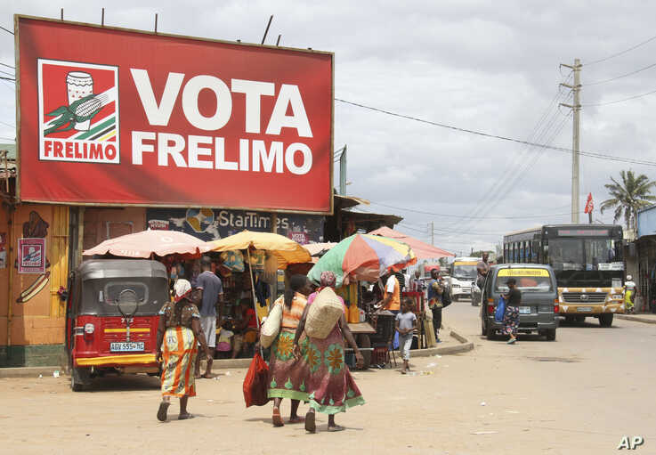 In this photo taken Friday, Oct. 11, 2019, women walk beneath an election banner for the ruling Frelimo Party in Maputo,…
