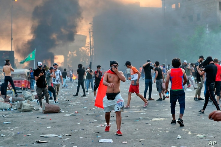 Anti-government protesters set fires and close a street during a demonstration in Baghdad, Iraq, Thursday, Oct. 3, 2019. Iraqi…