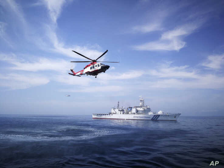 This photo released by Malaysian Maritime Enforcement Agency shows the Japan Coast Guard ship Tsugaru (PLH02) and helicopters…