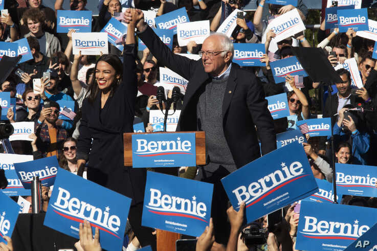 Democratic presidential candidate Sen. Bernie Sanders, I-Vt., right, is introduced by Rep. Alexandria Ocasio-Cortez, D-N.Y.,…