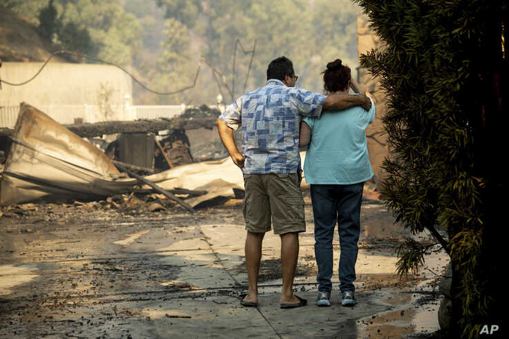 Eyed Jarjour, left, comforts a neighbor who lost her Jolette Ave. home to the Saddleridge Fire on Friday, Oct. 11, 2019, in…