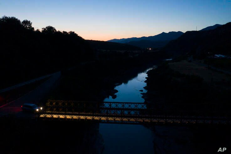 In this June 30, 2019 photo, the sky is reflected in the Vjosa River after sunset near the village of Badelonje, Albania…