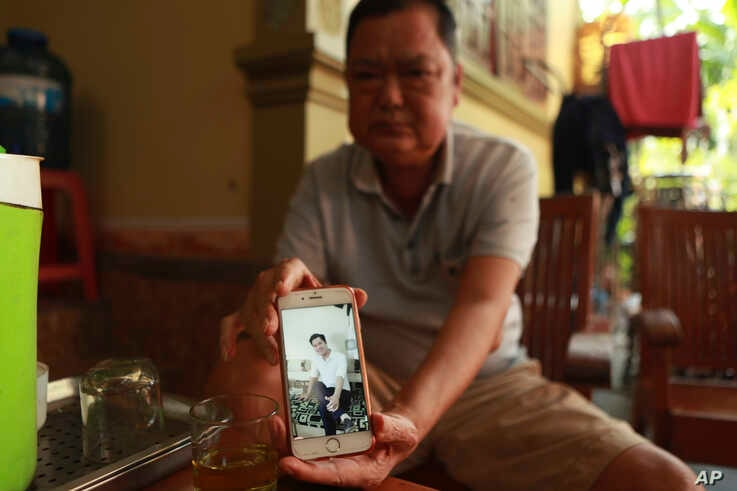 Nguyen Thanh Le holds up his phone showing a photo of his son Nguyen Van Hung on Monday, Oct. 28, 2019, in Dien Chau district,…