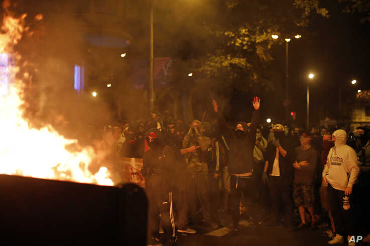 Protestors stand by a burning barricade in Barcelona, Spain, Saturday, Oct. 19, 2019. Radical separatists have clashed with…
