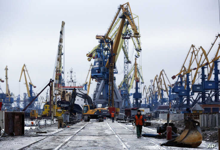 Workers pass in Mariupol trade port in Mariupol, south coast of Azov sea, eastern Ukraine, Sunday, Dec. 2, 2018. President…