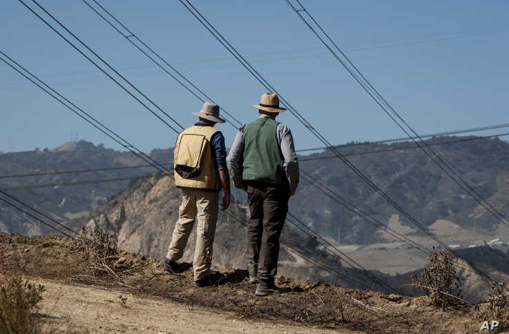 FILE - In this Oct. 15, 2019, file photo, fire investigators examine the scene around a transformer tower in Sylmar, Calif.,…