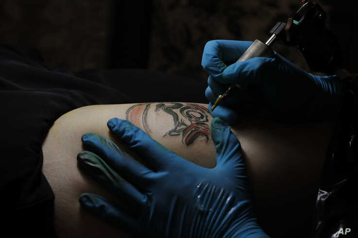 In this Wednesday, Oct. 23, 2019, photo, tattoo artist Mike Chan's needle buzzes gently as he draws a design on his customer's…