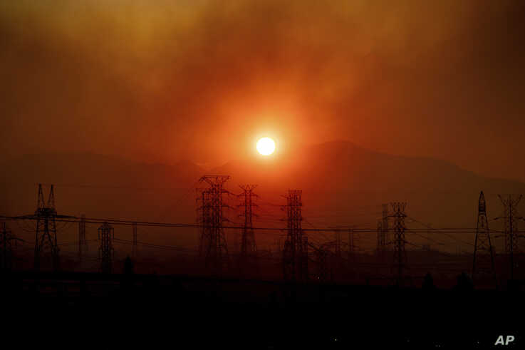 Smoke from the Saddleridge Fire hangs above power lines as the sun rises in Newhall, Calif., on Friday, Oct. 11, 2019. An…