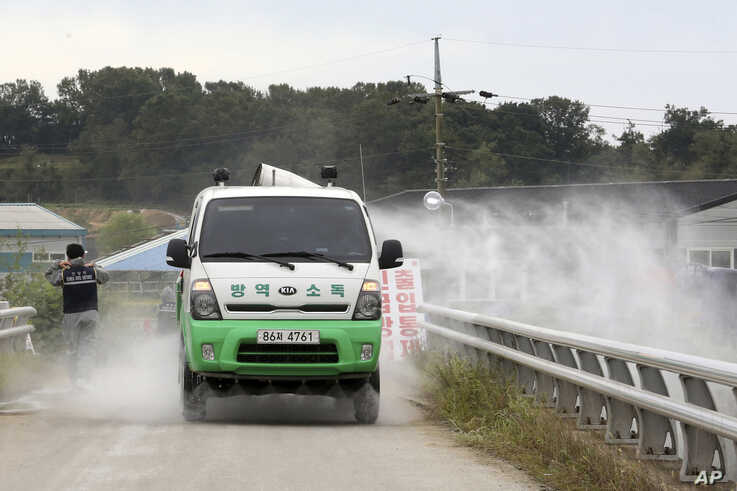 Disinfectant solution is sprayed from a vehicle as a precaution against African swine fever near a pig farm in Paju, South…