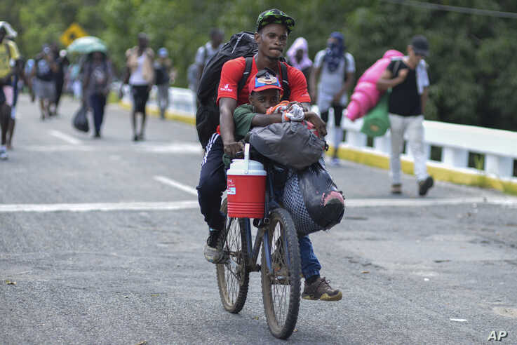 Two migrants bike down Highway 200 en route to Huixtla with all their belongings near Tapachula, Chiapas state, Mexico,…