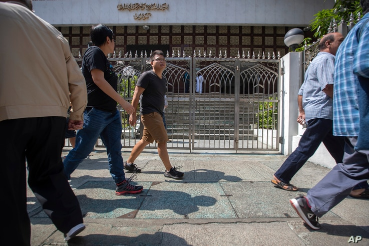 Pedestrians walk past a blue-stained sidewalk outside the Kowloon Mosque in Hong Kong